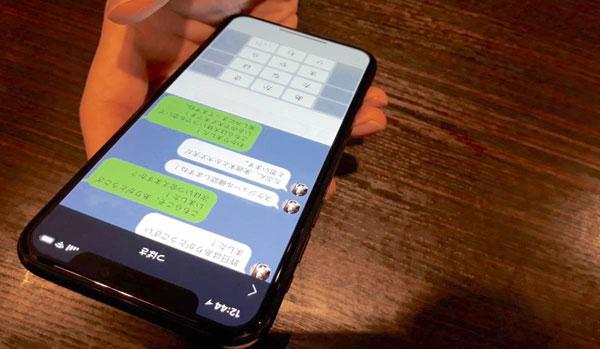 彼氏の手元のスマートフォンに映るLINEのトーク画面