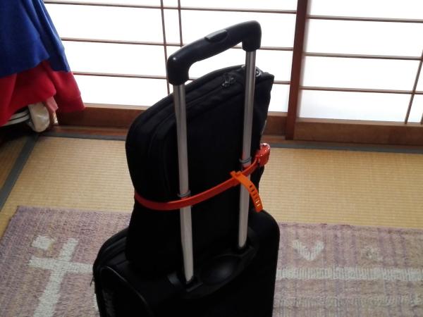 「OTTOLOCK」旅行用キャリーケースの上にノートパソコンが入ったカバンを置いて縛った様子