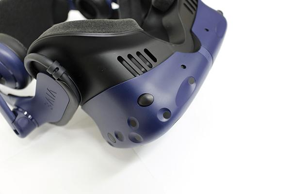 HMD前面左下のボタンでヘッドセット内の空間を広げることが可能、眼鏡を着けた状態でも問題なく装着できるようだ ※VIVE Proを逆さにして撮影