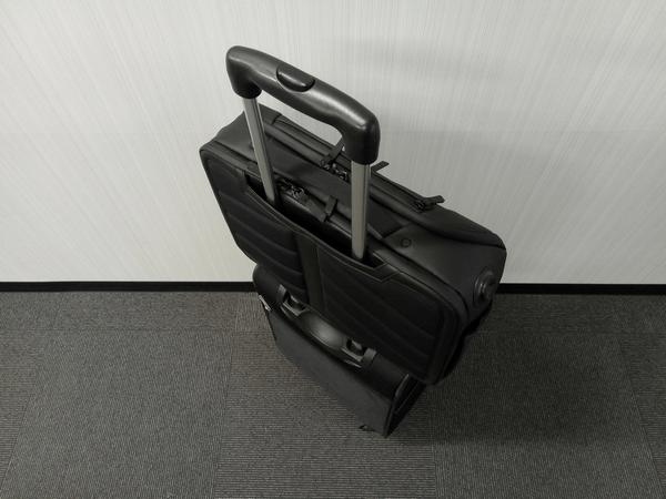 NOMATICシリーズメッセンジャーバッグをキャリーケースの持ち手に通した様子