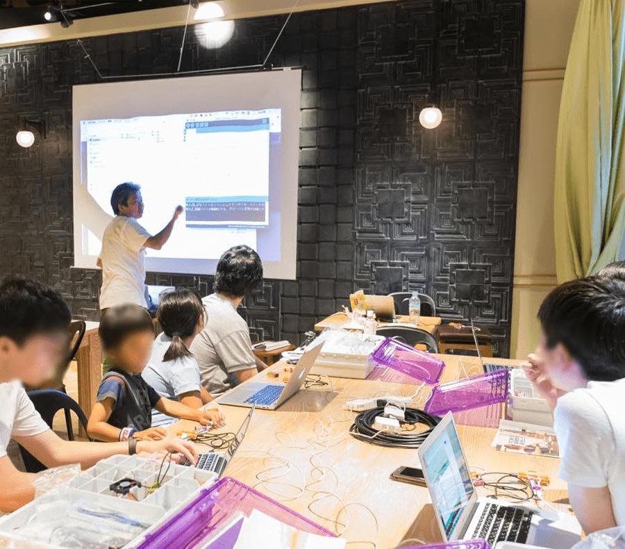 クスールが主宰する子ども向けプログラミング講座の様子より。画面の前に立っているのが松村さん。子どもたちが楽しんで参加できるlittleBits(リトルビッツ)を用いた電子工作の授業風景です